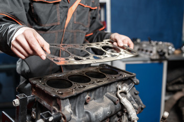 Sealing gasket in hand. The mechanic disassemble block engine vehicle. Engine on a repair stand with piston and connecting rod of automotive technology. Interior of a car repair shop.
