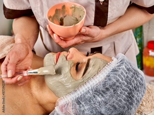 Collagen facial mask for skin treatment. Face of woman of elderly woman 50-60 years old receiving cosmetic procedure in beauty salon close up . Professional beautician. Removing black dots.