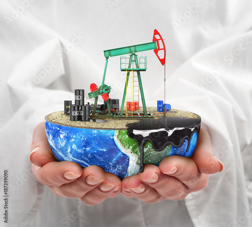 Foto Murales Eco-concept. A cut planet with oil pumpjack in woman's hands isolated on a white background. The concept of natural resource extraction.