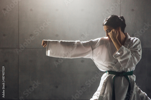 Foto Murales Martial arts Concept. Young woman in kimono practicing karate