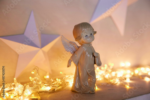 statue of an angel on the background of a New Year's garland - 187420074