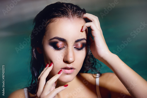 Brunette girl in the pool with bright makeup with hands on the head of hair close-up