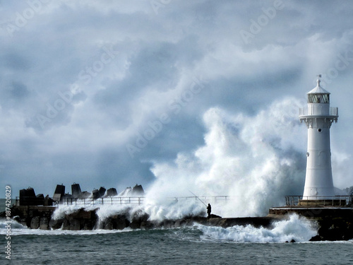 Fotobehang Natuur Fisherman fishing below light house in stormy sea