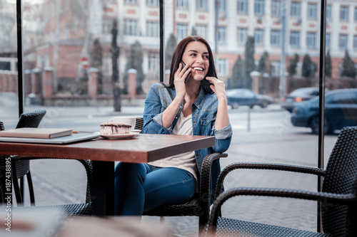 Love this place. Attractive brunette keeping smile on her face and turning head while sitting in cafe