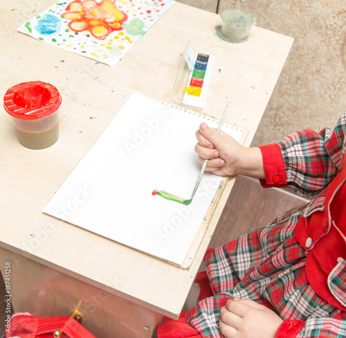 Foto Murales A girl draws a drawing with paints on a sheet