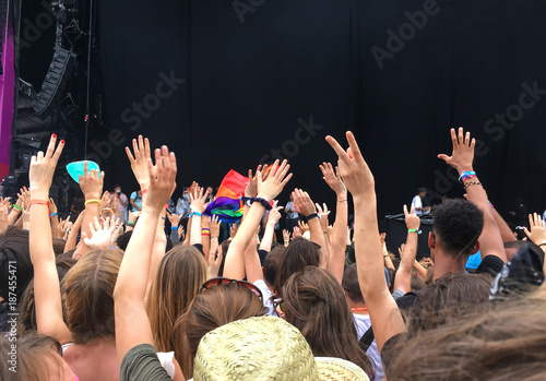 Audience with hands raised at a music festival, empty stage with copy space in the background - 187455471