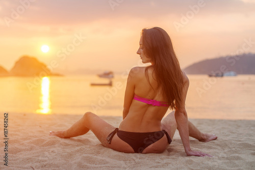 Foto op Canvas Snelle auto s Rear view of slim female model sitting on seashore wearing bikini looking away during sunrise with sun path reflected water