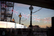 Dolphin lamp posts and London Eye reflecting in a kiosk window on the Queens Walk promenade on the southern bank of the River Thames in London England