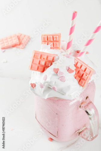 Tuinposter Milkshake Crazy shake, romantic milkshake for Valentine's day with strawberry, white chocolate and sugar candy hearts, on white background, copy space