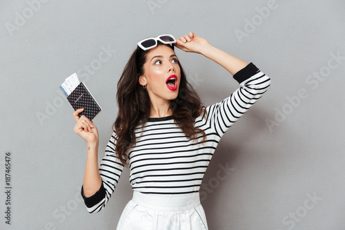 Foto Murales Portrait of a shocked woman holding passport
