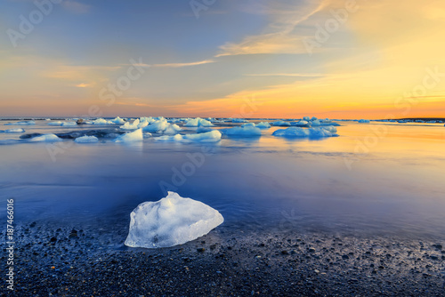 Foto auf Acrylglas See sonnenuntergang Coast of the Atlantic Ocean. The ice floe on a black sandy beach and floating ice floes in the water at sunset. Long exposure. Iceland.