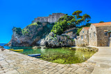 Fort Dubrovnik beach summer. / Scenic view at old fort in Dubrovnik with marble beach in foreground. - 187478042