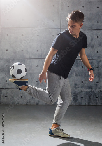 Fotobehang Voetbal Football freestyle. Young man practices with soccer ball