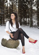 Attractive beautiful sexy young woman outdoors in the snow in winter in white blouse, shorts, leggings and red high heels