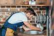 side view of young handyman repairing sink in kitchen