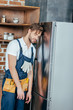 tired young foreman with tool belt leaning at broken refrigerator