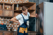 repairman suffering from backache while fixing refrigerator