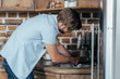 side view of young man repairing sink at home