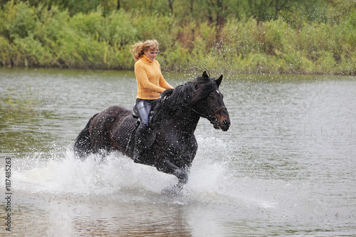 Foto Murales Blonde woman riding horseback in a shallow riverbed