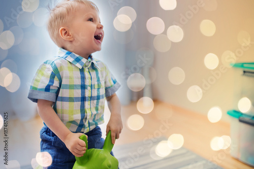 happy baby boy playing with ride-on toy at home