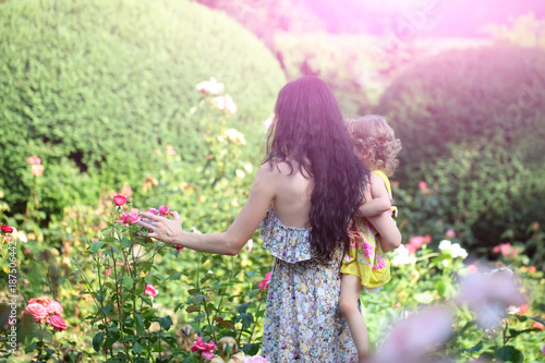 Fotobehang Purper Woman hold child girl at blossoming roses on idyllic day