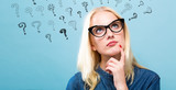 Young woman in a thoughtful pose with question marks - 187526412