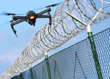 Drone monitoring barbed wire fence on state border or restricted area. Modern technology for security. - 187534016