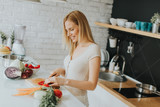 Pretty young woman preparing healthy meal in the modern kitchen - 187544693