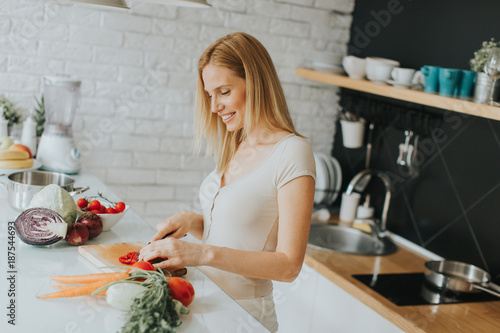 Pretty young woman preparing healthy meal in the modern kitchen