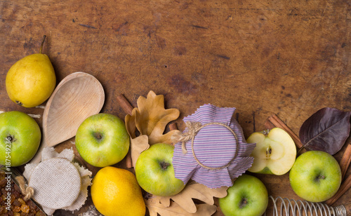 Autumn fruit background. Thanksgiving seasonal fruit. Stylish composition of green apple, oak leaves, pear, cinnamon, raisins, fabric cover, spoon, whisk. Old wood. Flat lay. Top view. - 187549236