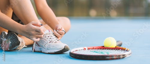 Fotobehang Tennis Tennis player tying shoelaces in court