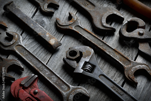 Dirty set of hand tools on a wooden background. Old rusty tools Sales tools for assembly workers. Old shop Old working. Vintage working tools (drill, saw, ruler and others) on wooden background