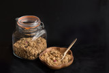 A bowl and a jar with muesli on the black background - 187589844