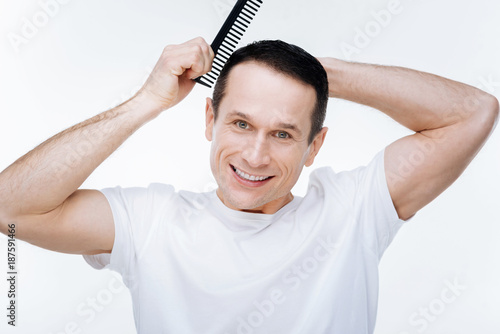 Deurstickers Kapsalon Perfect appearance. Cheerful delighted nice man using a comb and smiling while wanting to look perfect