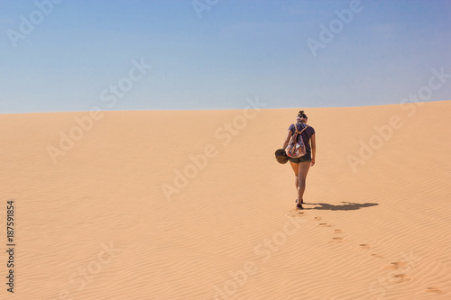 back view of lonely woman with backpack walking in desert, Vietnam, Phan Thiet