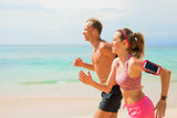 Couple using wearable devices while jogging on the beach - 187592656