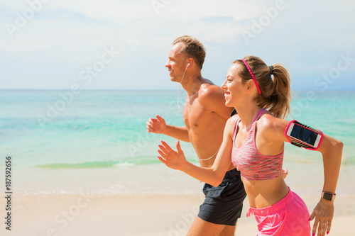Foto Murales Couple using wearable devices while jogging on the beach