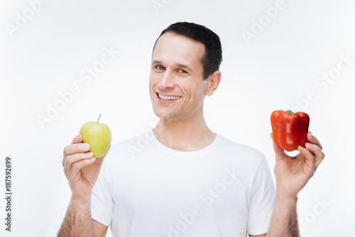 Foto Murales Delicious fruit. Handsome pleasant healthy man holding an apple and looking at it while eating healthy