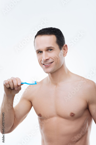 Beautiful smile. Cheerful nice handsome man holding a toothbrush and smiling while brushing his teeth in the morning - 187593445