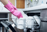housewife taking out clean dishware from dishwasher at home kitchen - 187601847