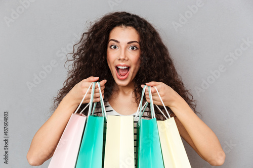 Papiers peints Kiev Close up portrait of excited female shopaholic making shopping being happy and delighted to buy favourite goods holding purchases in hands