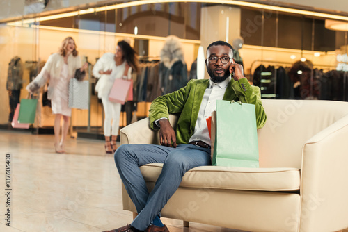 stylish african american man talking by smartphone while sitting with shopping bags in mall