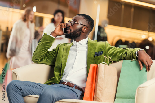 handsome african american man talking by smartphone while sitting with shopping bags in mall