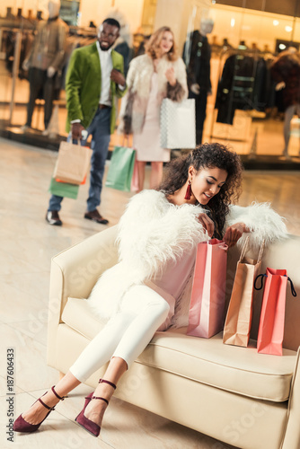 smiling fashionable african american woman in stylish fur coat sitting with paper bags in shopping mall