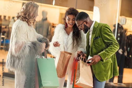 happy stylish multiethnic people looking into shopping bags in mall