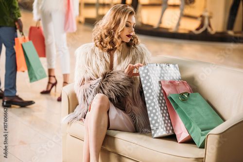 stylish young woman in fur coat sitting with shopping bags in mall