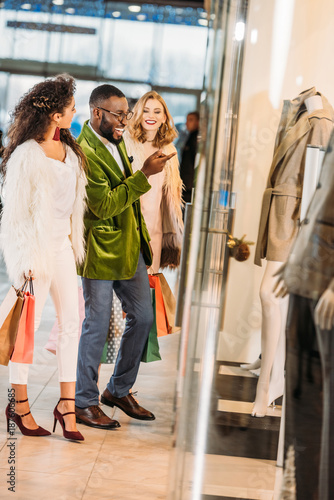side view of smiling fashionable multiethnic people shopping together in mall