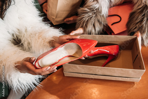 cropped shot of girls in trendy fur coats holding box with stylish high heeled shoes