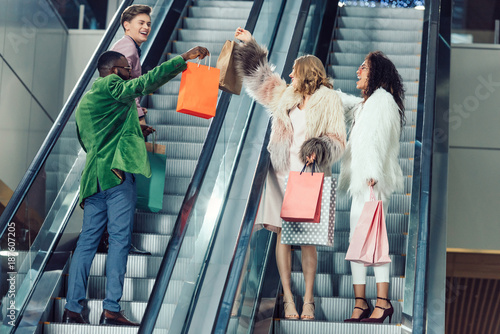 stylish young male and female shoppers on escalators at mall