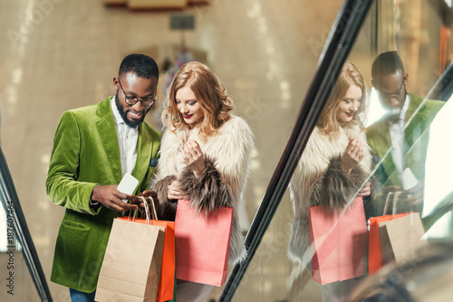 happy young couple riding escalator at shopping mall